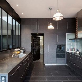 パリの大きいコンテンポラリースタイルのおしゃれなキッチン (一体型シンク、フラットパネル扉のキャビネット、濃色木目調キャビネット、ステンレスカウンター、メタリックのキッチンパネル、アイランドなし、メタルタイルのキッチンパネル、パネルと同色の調理設備、セラミックタイルの床) の写真