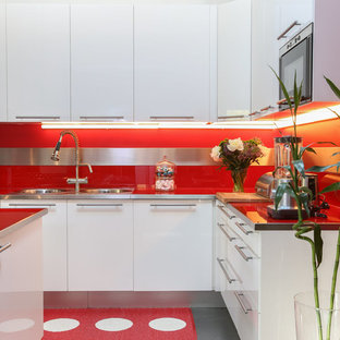 Large industrial eat-in kitchen photos - Inspiration for a large industrial l-shaped concrete floor and gray floor eat-in kitchen remodel in Paris with an undermount sink, beaded inset cabinets, white cabinets, glass countertops, red backsplash, mirror backsplash, stainless steel appliances, an island and red countertops