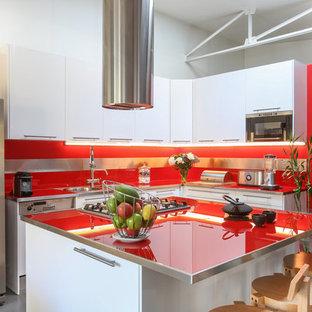 Aménagement d'une grande cuisine contemporaine en L avec un évier encastré, des portes de placard blanches, un plan de travail en verre, une crédence rouge, un électroménager en acier inoxydable, béton au sol, un îlot central, un sol gris, un plan de travail rouge, un placard à porte plane et une crédence en feuille de verre.