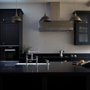 ロンドンの中サイズのヴィクトリアン調のおしゃれなキッチン (無垢フローリング、ベージュの床、黒いキッチンカウンター) の写真