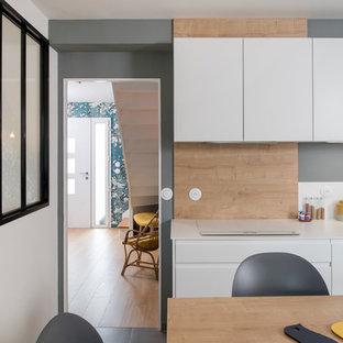リヨンの中サイズのモダンスタイルのおしゃれなキッチン (一体型シンク、フラットパネル扉のキャビネット、白いキャビネット、ラミネートカウンター、ベージュキッチンパネル、木材のキッチンパネル、パネルと同色の調理設備、セラミックタイルの床、グレーの床、白いキッチンカウンター) の写真