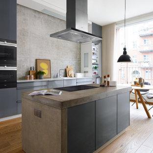 Cette image montre une cuisine ouverte parallèle design avec des portes de placard grises, un plan de travail en béton, une crédence grise, un électroménager encastrable, un sol en bois brun, un îlot central, un sol marron et un plan de travail gris.