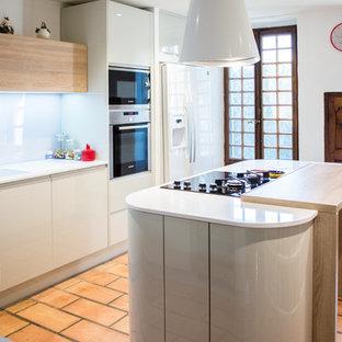 リヨンの広いモダンスタイルのおしゃれなキッチン (ダブルシンク、インセット扉のキャビネット、ベージュのキャビネット、珪岩カウンター、白いキッチンパネル、ガラス板のキッチンパネル、シルバーの調理設備、レンガの床、赤い床) の写真
