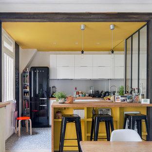 Immagine di una piccola cucina design con lavello a doppia vasca, ante a filo, ante bianche, top in legno, paraspruzzi grigio, paraspruzzi con piastrelle di metallo, elettrodomestici neri, pavimento in cementine, isola e pavimento multicolore
