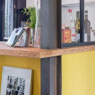 パリの小さいコンテンポラリースタイルのおしゃれなキッチン (ダブルシンク、インセット扉のキャビネット、白いキャビネット、木材カウンター、グレーのキッチンパネル、メタルタイルのキッチンパネル、黒い調理設備、セメントタイルの床、マルチカラーの床) の写真