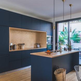 Réalisation d'une cuisine américaine parallèle design avec un évier 2 bacs, un placard à porte plane, des portes de placard bleues, un plan de travail en bois, une crédence marron, une crédence en bois, un électroménager encastrable, un sol en bois brun, un îlot central, un sol marron et un plan de travail marron.