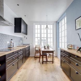 Exemple d'une cuisine américaine parallèle chic avec un placard avec porte à panneau encastré, des portes de placard noires, un plan de travail en bois, une crédence multicolore, un sol en bois clair, un sol beige et un plan de travail beige.