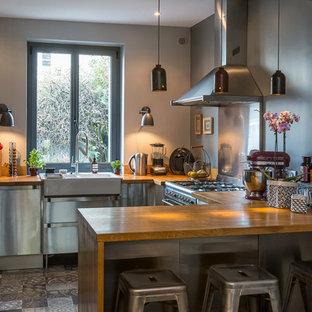 Aménagement d'une cuisine américaine éclectique en U de taille moyenne avec une façade en inox, une péninsule, un évier intégré, un sol en carreaux de ciment et un sol gris.
