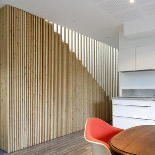 Inspiration pour une cuisine américaine linéaire design de taille moyenne avec des portes de placard blanches, une crédence grise et un sol en bois brun.