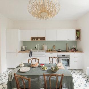 На фото: большая линейная кухня с двойной раковиной, белыми фасадами, столешницей из дерева, зеленым фартуком, полом из цементной плитки и разноцветным полом без острова с