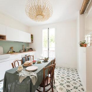 Offene, Einzeilige, Große Küche ohne Insel mit Doppelwaschbecken, flächenbündigen Schrankfronten, weißen Schränken, Arbeitsplatte aus Holz, Küchenrückwand in Grün, Zementfliesen und buntem Boden in Paris