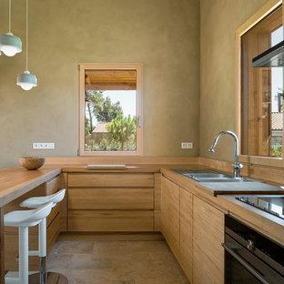 ボルドーのカントリー風おしゃれなキッチン (フラットパネル扉のキャビネット、淡色木目調キャビネット、木材カウンター、トラバーチンの床、ダブルシンク、ベージュの床) の写真