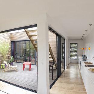 Idée de décoration pour une cuisine ouverte linéaire design de taille moyenne avec un évier posé, un placard à porte plane, des portes de placard blanches, aucun îlot et un sol en bois clair.