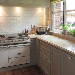 リールの中サイズのカントリー風おしゃれなマルチアイランドキッチン (アンダーカウンターシンク、ベージュのキャビネット、白いキッチンパネル、磁器タイルのキッチンパネル、カラー調理設備、テラコッタタイルの床、赤い床、ベージュのキッチンカウンター) の写真