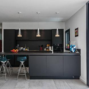 Idées déco pour une grande cuisine américaine parallèle contemporaine avec des portes de placard noires.
