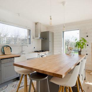 Idées déco pour une cuisine campagne avec un évier de ferme, un placard à porte shaker, des portes de placard grises, un plan de travail en bois, une crédence blanche, un électroménager encastrable, un sol en bois clair, un îlot central, un sol beige et un plan de travail marron.
