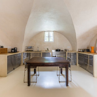 Design ideas for an u-shaped eat-in kitchen in Strasbourg with a drop-in sink, flat-panel cabinets, stainless steel cabinets, stainless steel appliances, no island, beige floor and beige benchtop.