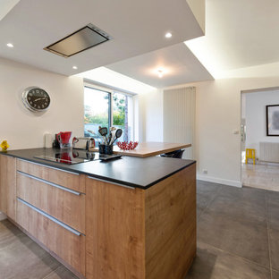 Photo of a mid-sized contemporary l-shaped eat-in kitchen in Lyon with an undermount sink, flat-panel cabinets, medium wood cabinets, black splashback, slate splashback, stainless steel appliances, travertine floors, with island, beige floor and black benchtop.