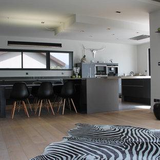 Idée de décoration pour une grande cuisine ouverte parallèle design avec un sol en bois clair, des portes de placard grises et un îlot central.