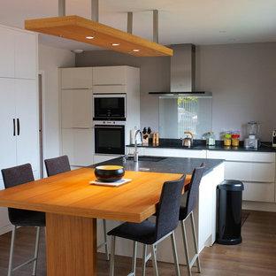 Idée de décoration pour une grande cuisine américaine parallèle design avec des portes de placard blanches et un îlot central.
