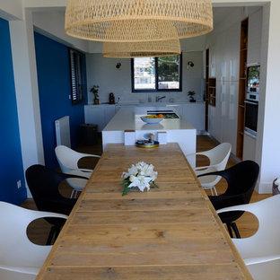 Modern inredning av ett stort vit linjärt vitt kök med öppen planlösning, med en integrerad diskho, släta luckor, vita skåp, bänkskiva i koppar, vitt stänkskydd, stänkskydd i keramik, rostfria vitvaror, plywoodgolv, en köksö och gult golv