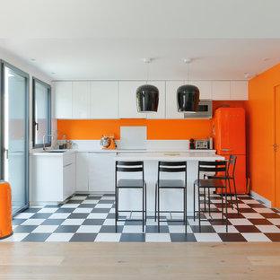 Idée de décoration pour une cuisine design en L avec un placard à porte plane, des portes de placard blanches, un électroménager de couleur, un îlot central, un sol multicolore et une crédence blanche.