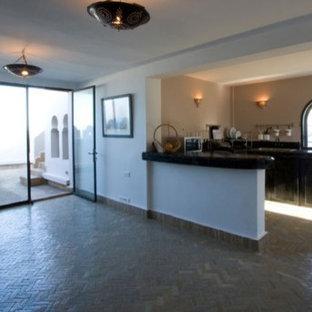 パリの地中海スタイルのおしゃれなアイランドキッチン (インセット扉のキャビネット、タイルカウンター、黒いキッチンパネル、テラコッタタイルのキッチンパネル、テラコッタタイルの床、黒いキッチンカウンター) の写真