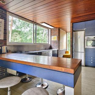 Cette image montre une cuisine vintage avec un placard à porte plane, des portes de placard bleues, un plan de travail en bois, une crédence métallisée, un électroménager en acier inoxydable, une péninsule et un sol marron.