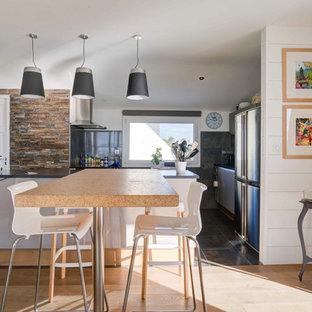 Exemple d'une cuisine américaine bord de mer en L avec un placard à porte plane, des portes de placard grises, une crédence grise, un électroménager en acier inoxydable, une péninsule, un sol gris et un plan de travail marron.