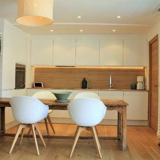 Cette image montre une cuisine américaine design en L avec un placard à porte plane, des portes de placard blanches, une crédence marron, un sol en bois brun et un sol marron.
