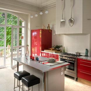Inspiration pour une cuisine américaine parallèle design de taille moyenne avec un placard à porte plane, des portes de placard rouges, un électroménager en acier inoxydable et un îlot central.