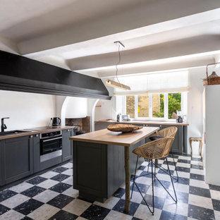 Идея дизайна: прямая кухня-гостиная среднего размера в стиле фьюжн с серыми фасадами, белым фартуком, полом из терраццо, островом, разноцветным полом и коричневой столешницей