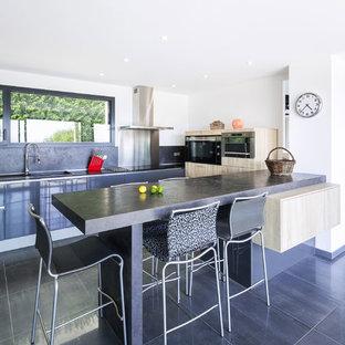 Cette image montre une cuisine design en U avec un placard à porte plane, des portes de placard noires, une crédence noire, une péninsule, un sol noir et un plan de travail noir.