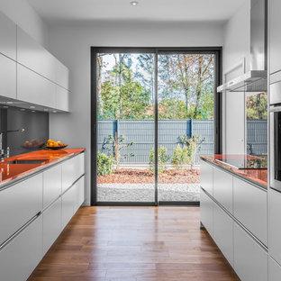 Bild på ett funkis orange oranget parallellkök, med en undermonterad diskho, släta luckor, vita skåp, bänkskiva i glas, grått stänkskydd, glaspanel som stänkskydd, rostfria vitvaror och mellanmörkt trägolv
