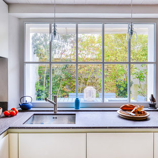 Exemple d'une cuisine ouverte moderne en U de taille moyenne avec un évier encastré, des portes de placard blanches, une crédence grise et une péninsule.