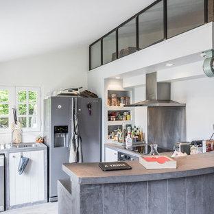 Aménagement d'une petite cuisine américaine industrielle en U avec des portes de placard blanches, un plan de travail en béton, une crédence métallisée, un électroménager en acier inoxydable et une péninsule.