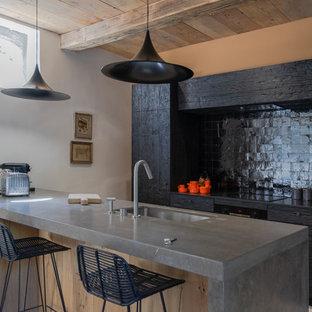 マルセイユの中くらいのカントリー風おしゃれなキッチン (アンダーカウンターシンク、ライムストーンカウンター、黒いキッチンパネル、テラコッタタイルのキッチンパネル、パネルと同色の調理設備、ライムストーンの床、グレーの床、グレーのキッチンカウンター、フラットパネル扉のキャビネット、黒いキャビネット) の写真