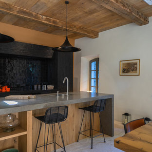 This is an example of a mid-sized country galley eat-in kitchen in Marseille with an undermount sink, beaded inset cabinets, dark wood cabinets, limestone benchtops, black splashback, terra-cotta splashback, panelled appliances, limestone floors, with island, grey floor and grey benchtop.