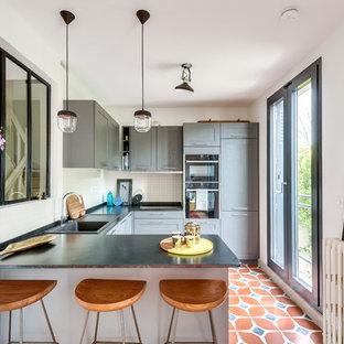 Idées déco pour une cuisine classique en U avec un évier posé, un placard à porte shaker, des portes de placard grises, une crédence blanche, un électroménager noir, une péninsule, un sol multicolore et un plan de travail noir.