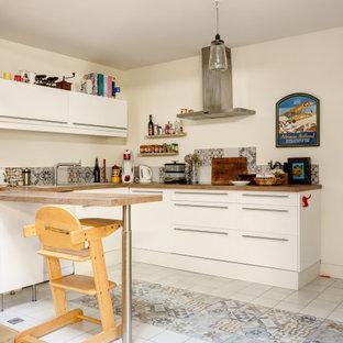 Aménagement d'une cuisine éclectique en U avec un placard à porte plane, des portes de placard blanches, une péninsule, un sol multicolore et un plan de travail blanc.