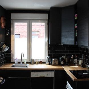 Inredning av ett minimalistiskt litet kök, med träbänkskiva, svart stänkskydd och laminatgolv