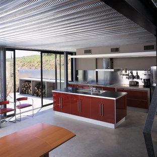Idee per una cucina industriale di medie dimensioni con ante lisce, ante rosse, top in cemento, paraspruzzi a effetto metallico, elettrodomestici in acciaio inossidabile, pavimento in cemento e isola