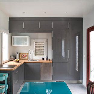 Cette photo montre une cuisine américaine tendance en L de taille moyenne avec un placard à porte plane, des portes de placard grises et un plan de travail en bois.