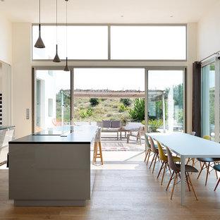 Idées déco pour une grand cuisine américaine parallèle contemporaine avec un évier encastré, un placard à porte plane, des portes de placard grises, un sol en bois clair, un îlot central et une crédence blanche.