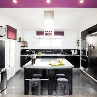 Große Moderne Wohnküche in L-Form mit Unterbauwaschbecken, Kassettenfronten, schwarzen Schränken, Edelstahl-Arbeitsplatte, Küchenrückwand in Schwarz, Rückwand aus Keramikfliesen, Küchengeräten aus Edelstahl, Keramikboden, Kücheninsel, grauem Boden und grauer Arbeitsplatte in Toulouse