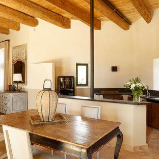 Réalisation d'une cuisine ouverte méditerranéenne de taille moyenne avec un évier encastré, une crédence noire, un sol beige, un placard à porte plane, des portes de placard en bois sombre, un électroménager noir, une péninsule, un sol en carreau de terre cuite et un plan de travail noir.