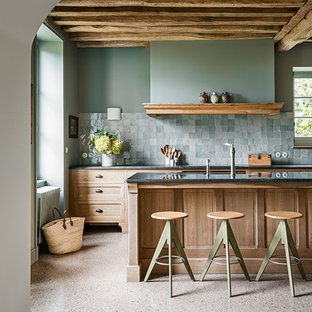 This is an example of a country kitchen in Paris with a farmhouse sink, shaker cabinets, light wood cabinets, green splashback and with island.