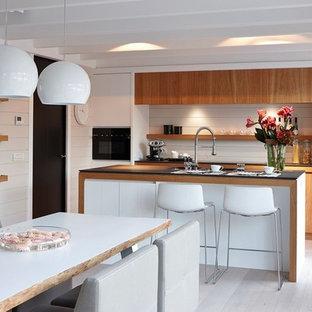 Réalisation d'une grand cuisine américaine parallèle vintage avec un placard à porte plane, des portes de placard en bois brun, un électroménager en acier inoxydable, un sol en bois clair et un îlot central.