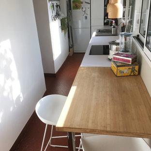 ナントの小さいモダンスタイルのおしゃれなキッチン (シングルシンク、白いキャビネット、ラミネートカウンター、白いキッチンパネル、ガラス板のキッチンパネル、黒い調理設備、テラコッタタイルの床、アイランドなし、赤い床) の写真
