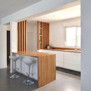 Idée de décoration pour une cuisine ouverte linéaire design de taille moyenne avec des portes de placard blanches, un plan de travail en bois, un sol gris, un évier 1 bac, un placard sans porte, une crédence marron, une crédence en bois, aucun îlot et un plan de travail marron.